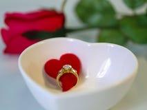 Anillo de diamante con el corazón rojo en un cuenco blanco de la forma del corazón entre el re Foto de archivo