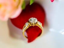 Anillo de diamante con el corazón rojo en un cuenco blanco de la forma del corazón entre el re Fotos de archivo libres de regalías