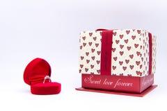 Anillo de diamante en la caja roja del corazón con la caja de regalo aislada en pizca Foto de archivo