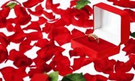 Anillo de diamante en una caja de la joyería en los pétalos de Rose Foto de archivo