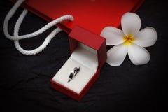 Anillo de diamante en una caja de regalo en fondo negro Imagen de archivo