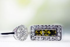 Anillo de diamante y anillo verde hermoso de la piedra preciosa, esperando para ser colocado en un fondo blanco foto de archivo