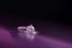 Anillo de oro blanco con los diamantes en fondo coloreado Fotografía de archivo