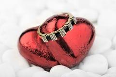 Anillo de oro con zafiros y diamantes en corazones rojos Fotos de archivo