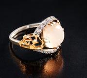 Anillo del oro con los diamantes y del ópalo en el fondo blanco fotos de archivo libres de regalías