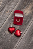 Anillo esmeralda del compromiso y corazones rojos Imagen de archivo