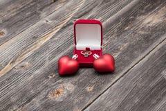 Anillo esmeralda del compromiso y corazones rojos Fotos de archivo libres de regalías