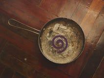 Anillo púrpura del mosquito en la cacerola vieja sucia del vintage - fondo de madera Imagen de archivo