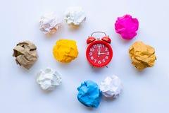 Anillo rojo del despertador con la bola de papel arrugada colorida aislada en el fondo blanco imagen de archivo libre de regalías