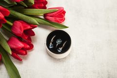 Anillo y pendientes con el topacio y diamantes en una caja blanca redonda en afilar el fondo gris y con un ramo de tulipanes rojo imagenes de archivo