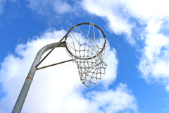 Anillo y red de la meta del netball contra un cielo azul y las nubes Foto de archivo