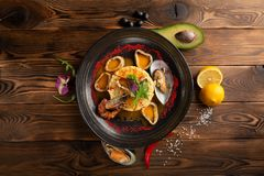 Anillos cocidos del calamar con arroz y especias en la placa negra fotos de archivo