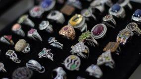 Anillos con las diversos piedras preciosas, materiales, tama?os y formas en la exhibici?n de una joyer?a foto de archivo