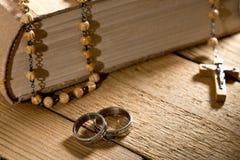 Anillos de bodas, biblia y gotas de rezo Fotografía de archivo