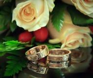 Anillos de bodas con el ramo. Foco en los anillos Foto de archivo