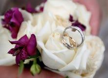 Anillos de bodas con la rosa en colores pastel del blanco, cierre para arriba Fotografía de archivo