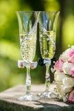 Anillos de bodas con las rosas y los vidrios de champán Fotografía de archivo libre de regalías