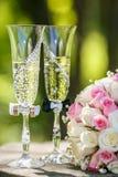 Anillos de bodas con las rosas y los vidrios de champán Fotos de archivo libres de regalías