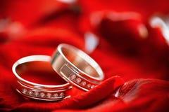 Anillos de bodas con los diamonts en un fondo de color rojo oscuro Imagen de archivo