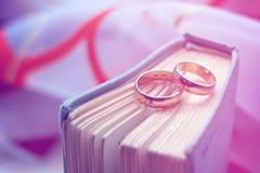 Anillos de bodas con un libro del vintage Fotografía de archivo