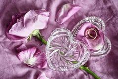 Anillos de bodas de oro en una caja de cristal bajo la forma de corazón y pétalos de rosas rosados Fondo de la boda Foto de archivo