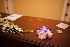 Anillos de bodas de un par nuevo-casado en un amortiguador para los anillos Foto de archivo libre de regalías