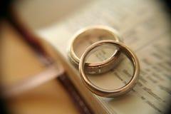 Anillos de bodas del oro blanco en la biblia Imagen de archivo