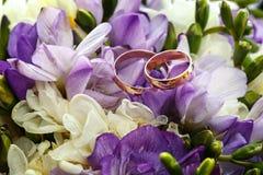 Anillos de bodas del oro en el ramo de flores para la novia Imagen de archivo