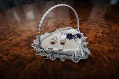 Anillos de bodas del oro en el soporte para los anillos en la forma de corazón Fotos de archivo