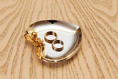 Anillos de bodas del oro en la placa brillante Imágenes de archivo libres de regalías