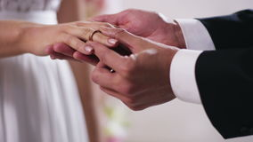 Anillos de bodas del oro y manos apenas del cierre casado de la pareja para arriba a mano de un hombre puesto en un anillo de com
