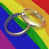 Anillos de bodas en bandera del arco iris Foto de archivo