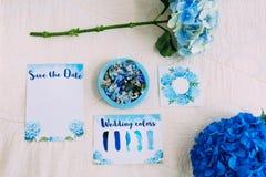 Anillos de bodas en caja azul al lado de la reserva la invitación de la fecha Endecha plana nupcial en colores azules ilustracion Fotografía de archivo
