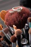 Anillos de bodas en cepillos del maquillaje Foto de archivo libre de regalías