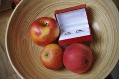 Anillos de bodas en el cuenco de fruta Fotografía de archivo libre de regalías