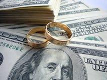 Anillos de bodas en el dinero Imagenes de archivo