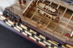 Anillos de bodas en el modelo de madera de la nave medieval Accesorios de novia y del novio Concepto marítimo Fotos de archivo libres de regalías