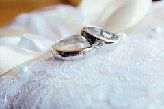 Anillos de bodas en la almohada del cordón Fotos de archivo
