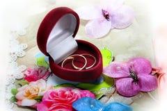 Anillos de bodas en la caja roja en la tarjeta de la invitación Fotos de archivo libres de regalías
