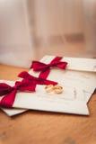 Anillos de bodas en la invitación con una cinta roja Fotos de archivo libres de regalías