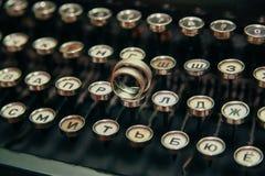Anillos de bodas en la máquina de escribir imagen de archivo