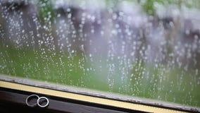 Anillos de bodas en la ventana en la lluvia Descensos sobre el vidrio Tes almacen de video
