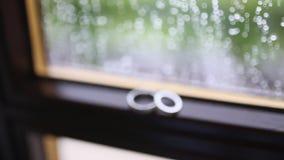 Anillos de bodas en la ventana en la lluvia Descensos sobre el vidrio Tes metrajes