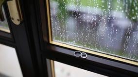 Anillos de bodas en la ventana en la lluvia Descensos sobre el vidrio Tes almacen de metraje de vídeo
