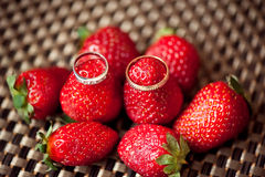Anillos de bodas en las fresas jugosas rojas Imágenes de archivo libres de regalías