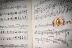 Anillos de bodas en los corazones de notes.music Imágenes de archivo libres de regalías