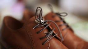 Anillos de bodas en los zapatos del ` un s de los hombres del marrón almacen de video