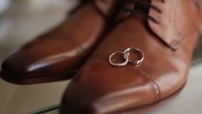 Anillos de bodas en los zapatos del ` un s de los hombres del marrón almacen de metraje de vídeo