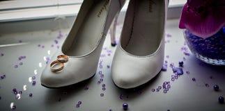 Anillos de bodas en los zapatos nupciales blancos Imágenes de archivo libres de regalías