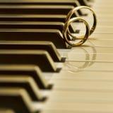 Anillos de bodas en piano Fotografía de archivo libre de regalías